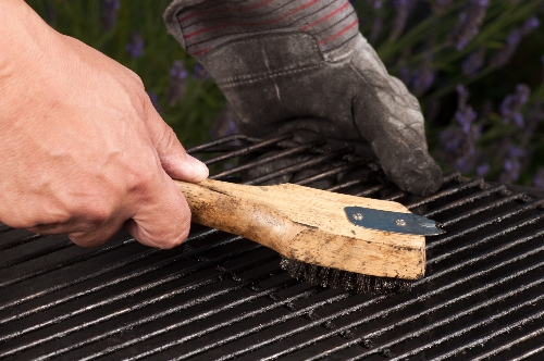 A grill owner uses a wire brush to scrub down their BBQ grill.